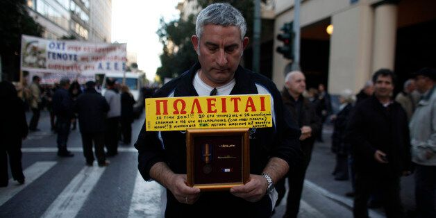 A Greek Army retiree holds his insignia and a for sale sign that
