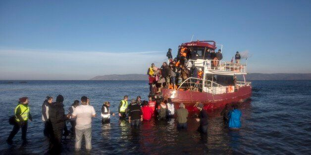 Volunteers help around 150 refugees and migrants, mostly from Syria and Iraq, to disembark from a vessel...
