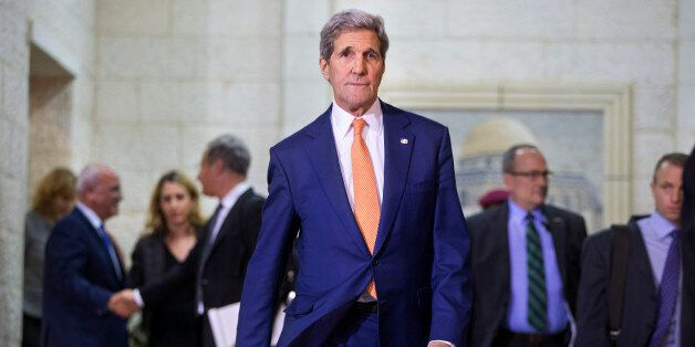 US Secretary of State John Kerry walks towards members of the media after meeting with Palestinian president...