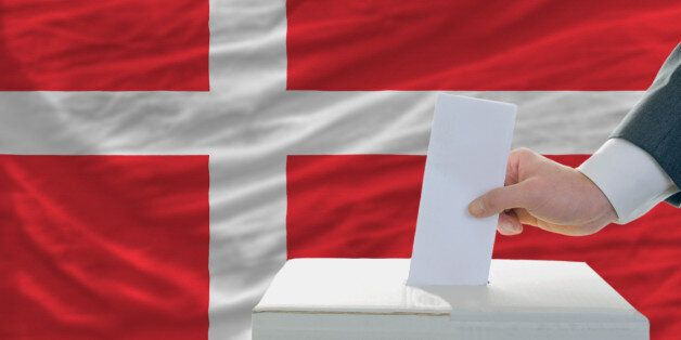 man putting ballot in a box during elections in denmark in fornt of