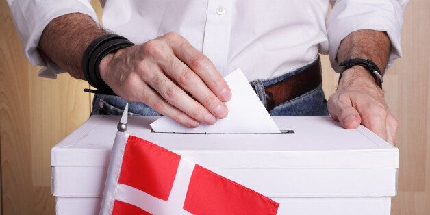 A man inserting a ballot to a ballot box. Danish flag in front of