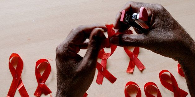 A HIV-positive person from the Support and Care Centre of the Sumanahalli Society prepares 'red ribbons'...