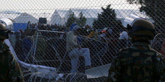 GEVGELIJA, MACEDONIA - DECEMBER 02: Macedonian policemen stand guard as refugees wait behind a fence...