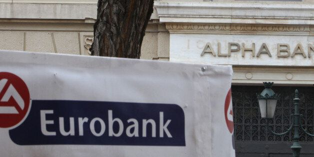 Alpha Bank and Eurobank logos are seen outside branches in Athens, Wednesday, March 14, 2012. Greece's...