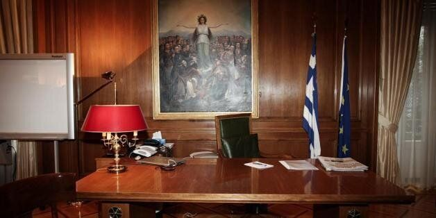 Greece's Prime Minister Alexis Tsipras speaks from his mobile phone during emergency Parliament session...
