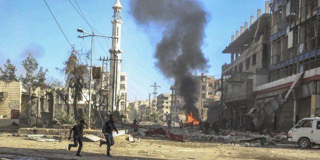 DAMASCUS, SYRIA - DECEMBER 4: Smoke rises as Syrians run away from a fire which broke out after the war...