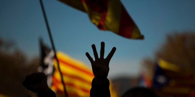 A pro Independence demonstrator gestures - four fingers symbolizing the four bars of the Catalonian flag,...