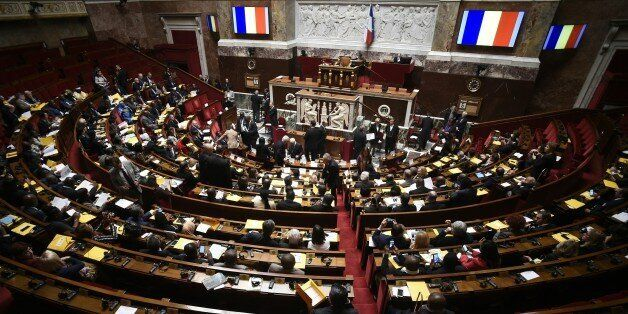 A picture taken on December 5, 2015 shows French flags on screens during a parliamentary meeting on the...
