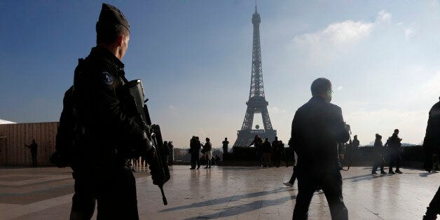 French police officers patrol near the Eiffel Tower, in Paris, Monday Nov. 23, 2015. French President...