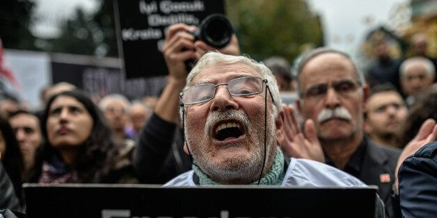 A member of journalism union holds a placard as he shouts slogans on November 29, 2015 in Istanbul during...