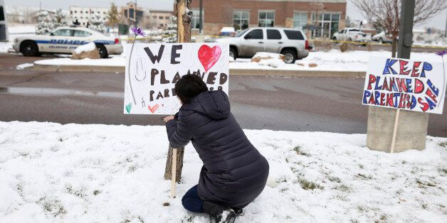 Bethany Winder, a nurse who lives in Colorado Springs, Colo., plants a sign in support of Planned Parenthood...