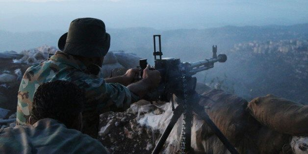 In this photo taken on Saturday, Oct. 10, 2015, Syrian army personnel fire a machine gun in Latakia province,...
