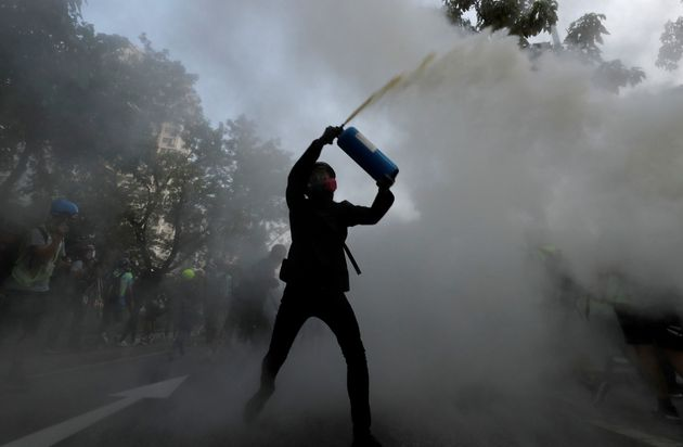 An anti-government protester uses a fire extinguisher during a march in Tuen Mun, Hong Kong...