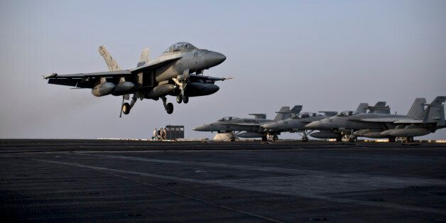 A U.S. Navy fighter jet is about to land on the flight deck of USS Theodore Roosevelt aircraft carrier,...