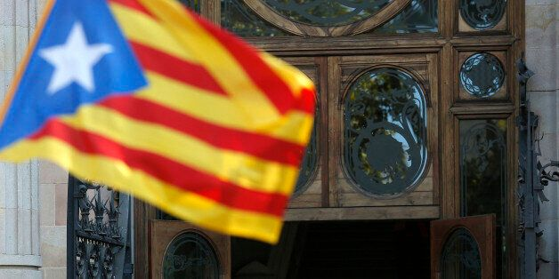 Regional acting President Artur Mas, center, waves to the crowd as he leaves Catalonia's high court after...