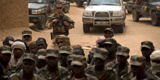 FILE - In this July 27, 2013 file photo, a French soldier stands watch behind Malian soldiers during...