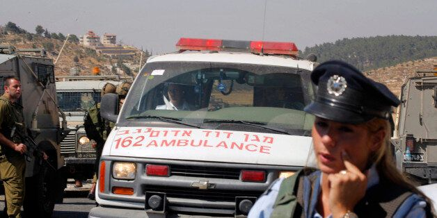 Israeli security forces stand around an ambulance in the area where three police officers were shot in...