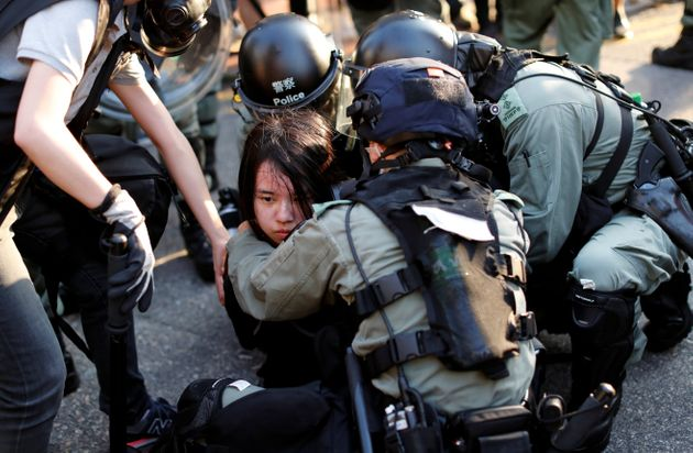An anti-government protester is detained during a march in Tuen Mun, Hong Kong Sept. 21,