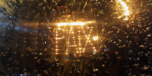 People gather around candles left in the shape of the word 'Peace' reflected through large mirror panels...