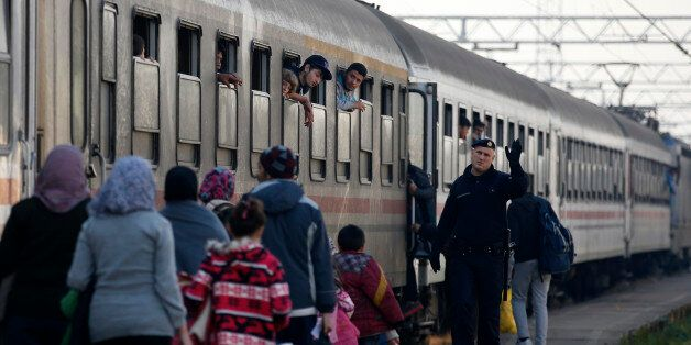 A Croatian police officer helps people board a train at the station in Sid, about 100 km west from Belgrade,...
