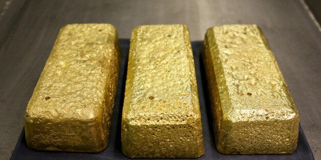 Three gold bars each weighing 25 kilogrammes sit on display at the Verninsky GOK gold mine and processing...