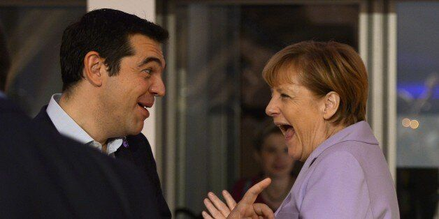 Germany's Chancellor Angela Merkel (R) talks to Greece's Prime minister Alexis Tsipras as she arrives...