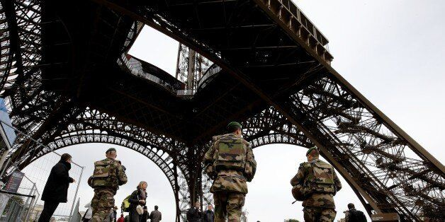 French soldiers patrol the area at the foot of the Eiffel Tower in Paris on November 14, 2015 following...