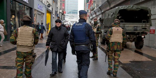 Belgian Army soldiers and police patrol an otherwise busy shopping street in Brussels on Saturday, Nov....