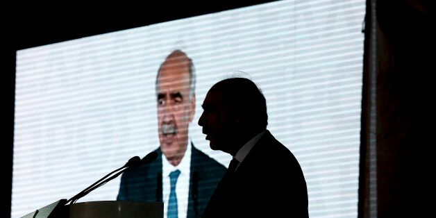 Evangelos Meimarakis, leader of the New Democracy Party of Greece, is silhouetted against a video screen...