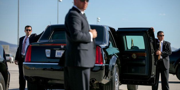 Secret Service agents stand around a presidential limo as President Barack Obama arrives at McCarran...