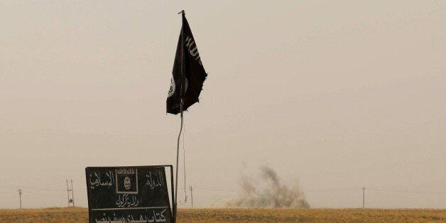 Smoke rises in the distance behind an Islamic State (IS) group flag and banner after Iraqi Kurdish Peshmerga...
