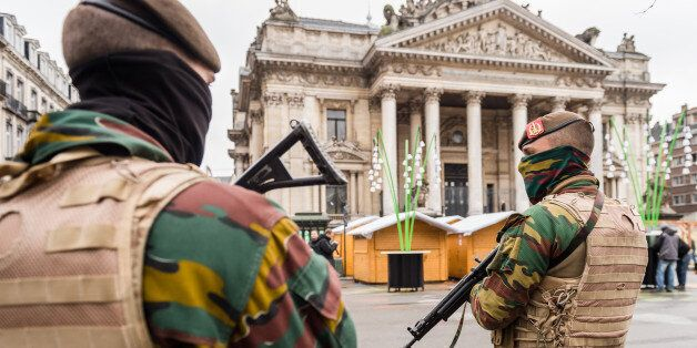 Belgian Army soldiers patrol near Christmas huts in front of the old Brussels' stock exchange on Sunday,...