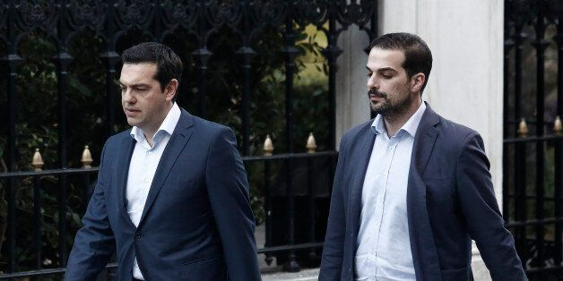 Alexis Tsipras, Greece's prime minister, left, and government spokesman Gabriel Sakelaridis, walk to...