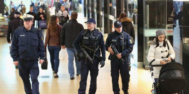 HANOVER, GERMANY - NOVEMBER 18: Heavily-armed German policemen patrol through a shopping passage inside...