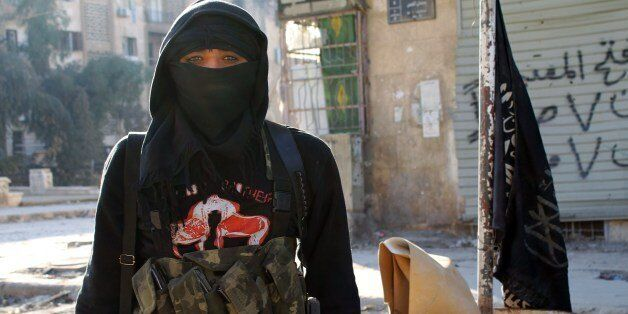 A member of jihadist group Al-Nusra Front stands in a street of the northern Syrian city of Aleppo on...