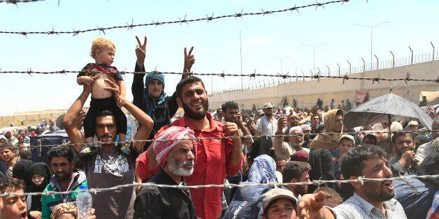 FILE - In this Monday, June 15, 2015 file photo, Syrian refugees gather at the Turkish border as they...