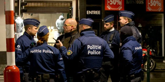 Police stand near a barricade during an operation in the center of Brussels on Sunday, Nov. 22, 2015....