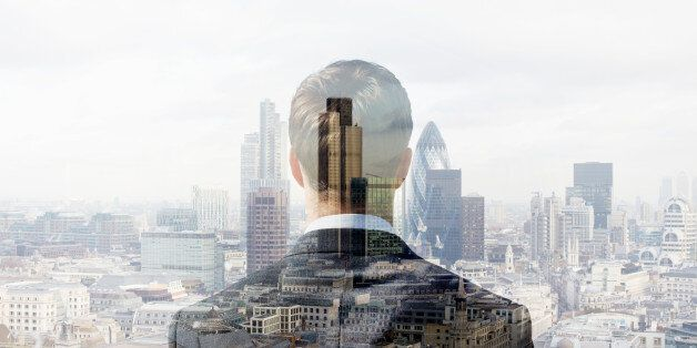 Double exposure of a business man looking towards the financial district of the City of London with the...