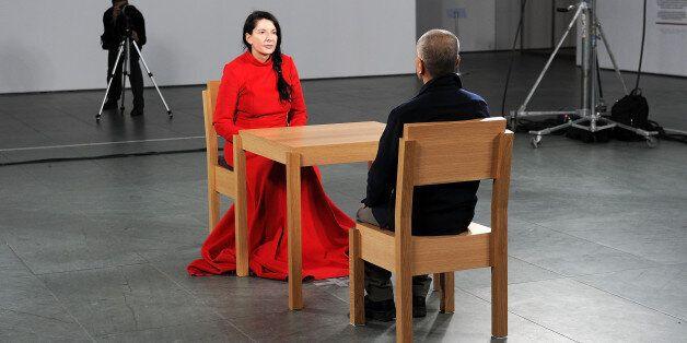 NEW YORK - MARCH 09: Artist Marina Abramovic (in red) performs during the 'Marina Abramovic: The Artist...