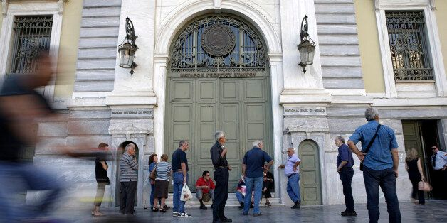 Pensioners queue to enter a National Bank of Greece SA bank branch to collect their pension payments...