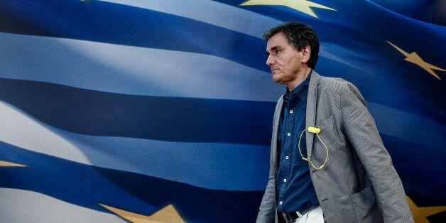 Euclid Tsakalotos, Greece's finance minister, walks towards the podium during a ministerial handover...