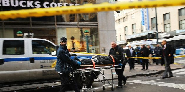 NEW YORK, NY - NOVEMBER 09: A body is brought up from a subway platform at the scene of a midtown shooting...