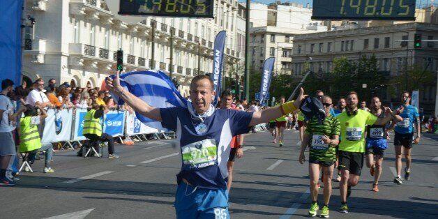 ATHENS, GREECE - 2015/05/03: A marathon runner finishes the Half Marathon holding a Greek flag. Over...