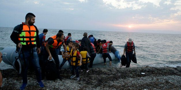 Syrian migrants arrive with an overcrowded dinghy from Turkish coasts at a Mytilene beach, on the northeastern...