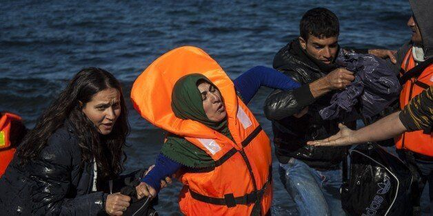 LESBOS ISLAND, GREECE - NOVEMBER 01: A group of refugees, succeeded to arrive the coast, are seen after...