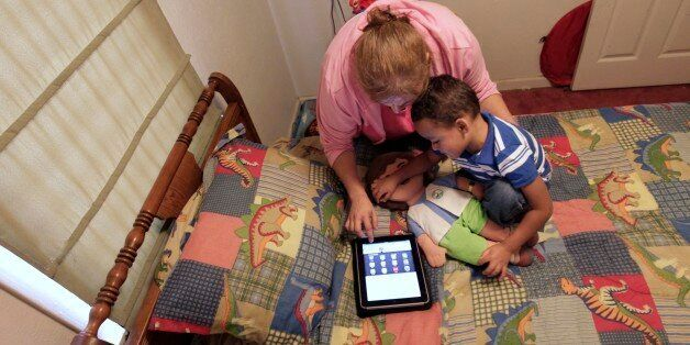 In this Friday, Oct. 21, 2011 photo, Denise Thevenot and her son Frankie Thevenot, 3, play with an iPad...