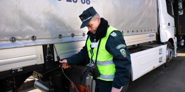 A Bulgarian border policeman checks the levels of oxygen in a truck to see if there is any illegal transport...