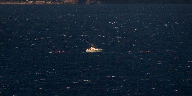 A Greek coast guard vessel tries to rescue refugees and migrants after the wooden boat they traveled...