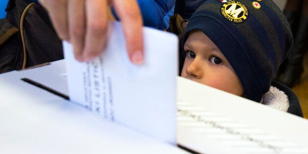 A child looks at a ballot being cast at a polling station in Zagreb, Croatia, Sunday, Nov. 8, 2015. Croatia's...