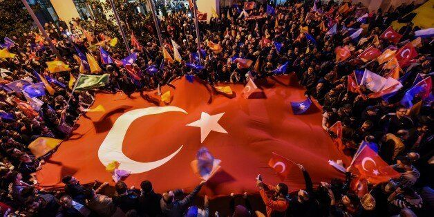 Supporters of Turkey's Justice and Development Party (AKP) hold a giant Turkish flag as they celebrate...